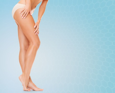 depilacion con cera: las personas, la salud y el concepto de belleza - mujer con las piernas largas en bragas de algodón que toca sus caderas sobre fondo azul