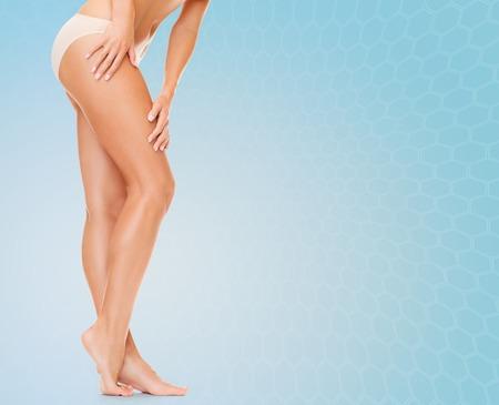 les gens, la santé et la beauté concept - femme avec de longues jambes dans des culottes en coton touchant ses hanches sur fond bleu
