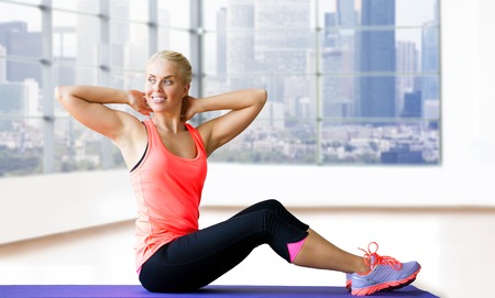 woman muscle: fitness, sport, exercising and people concept - smiling woman doing sit-up on mat over gym background