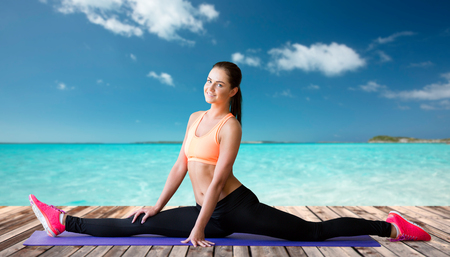 splits: fitness, sport, exercising, stretching and people concept - smiling woman doing splits on mat over sea and wooden berth at resort background