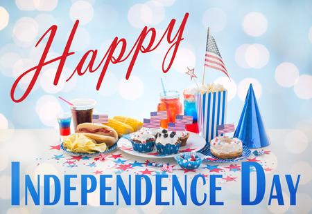 dog days: feliz día de la independencia, días de fiesta nacional, celebración, comida y patriotismo concepto - cerca de perro caliente con el americano decoración bandera, papas fritas y bebidas en 4 de julio en el partido casero