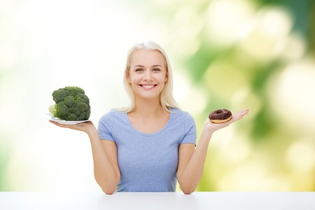good food: healthy eating, junk food, diet and choice people concept - smiling woman choosing between broccoli and donut over green natural background