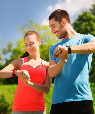 heart rate: fitness, sport, training, technology and lifestyle concept - two smiling people with heart rate watches outdoors