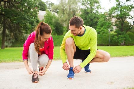 zapato: fitness, deporte, la amistad y el estilo de vida concepto - sonriendo par de atarse los cordones al aire libre