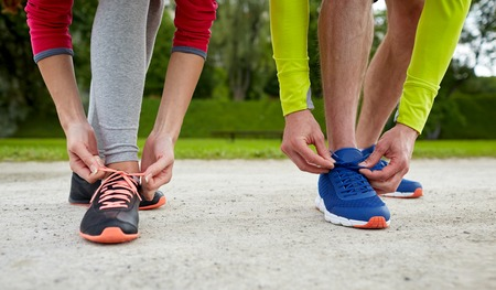 warm up: fitness, sport, friendship and lifestyle concept - close up of couple tying shoelaces outdoors