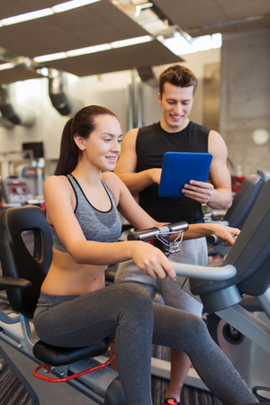 trainer: sport, fitness, lifestyle, technology and people concept - happy woman and trainer with tablet pc computer working out on exercise bike in gym Stock Photo