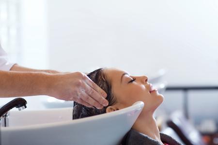Schönheit und Personen Konzept - glückliche junge Frau mit Friseur Waschkopf an Friseursalon Standard-Bild