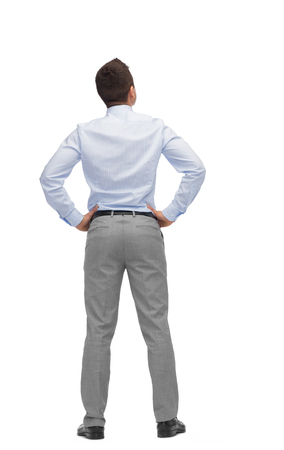 business, people, rear view and office concept - businessman looking up from back