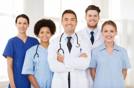 doctores: el hospital, la profesión, la gente y concepto de la medicina - grupo de médicos felices en el hospital