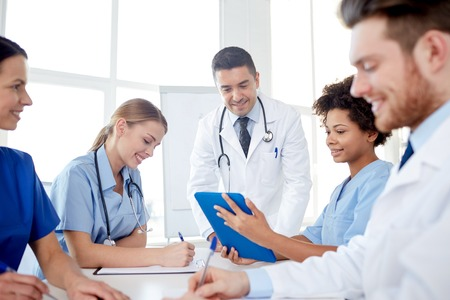 hospital notes: medical education, health care, people and medicine concept - group of happy doctors or interns with mentor meeting and taking notes at hospital