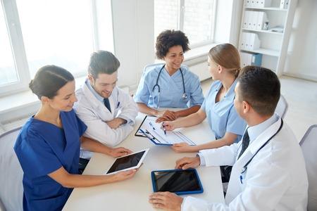 doctores: hospital, educación médica, la atención de la salud, las personas y el concepto de la medicina - grupo de médicos felices con las computadoras tablet pc reunión en la oficina médica Foto de archivo