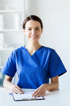 gezondheidszorg, beroep, mensen en geneeskunde concept - gelukkig vrouwelijke arts of verpleegkundige met klembord in het ziekenhuis