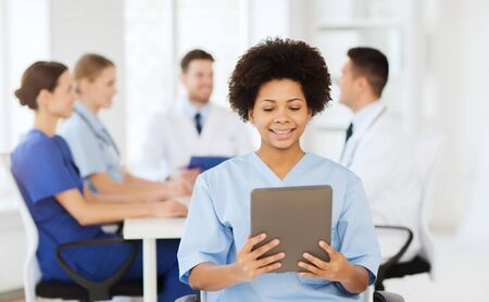 medics: clinic, profession, people and medicine concept - happy female doctor with tablet pc computer over group of medics meeting at hospital Stock Photo