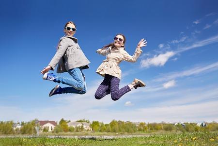 saltando: gente, ni�os, amigos y el concepto de la amistad - ni�as felices que saltan arriba al aire libre