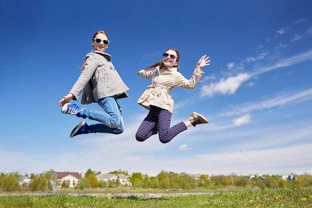 preteens girl: people, children, friends and friendship concept - happy little girls jumping high outdoors Stock Photo