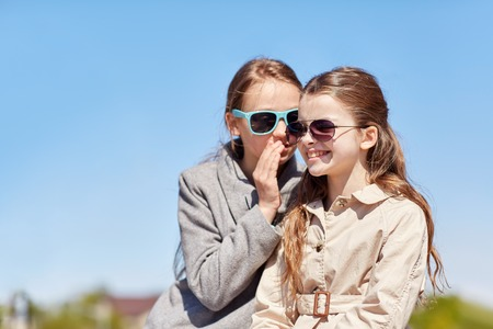 gossip: people, children and friendship concept - happy little girl in sunglasses whispering her secret to friends ear or gossiping outdoors