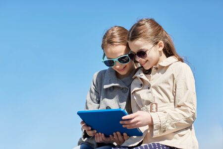 best friend: people, children, technology, friends and friendship concept - happy little girls in sunglasses with tablet pc computer outdoors