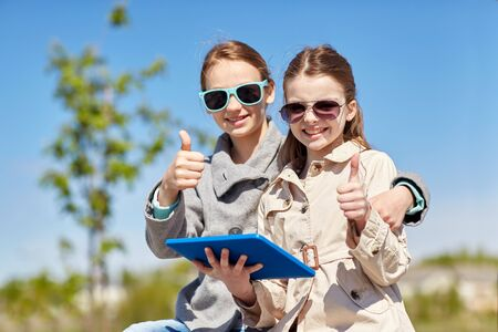 pre approval: people, children, technology, friends and friendship concept - happy little girls in sunglasses with tablet pc computer showing thumbs up outdoors
