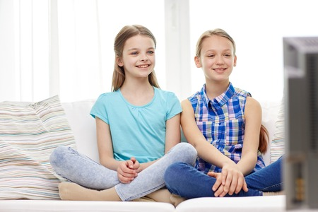 teenagers having fun: people, children, television, friends and friendship concept - two happy little girls watching tv at home
