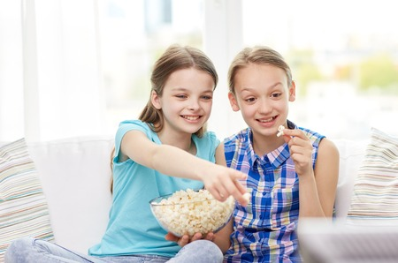 friends eating: people, children, television, friends and friendship concept - two happy little girls watching tv and eating popcorn at home Stock Photo