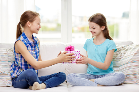 birthday present: people, children, holidays, friends and friendship concept - happy little girls with birthday present sitting on sofa at home