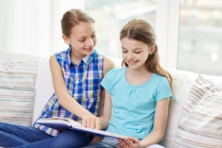 people, children, friends, literature and friendship concept - two happy girls sitting on sofa and reading book at home Stock Photo