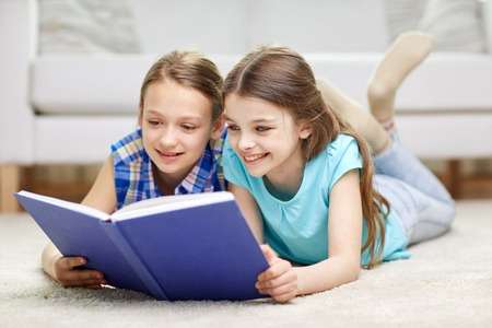 offsprings: people, children, friends, literature and friendship concept - two happy girls lying on floor and reading book at home