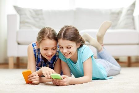 les gens, les enfants, la technologie, les amis et le concept d'amitié - petites filles heureuses avec les smartphones couché sur le plancher à la maison