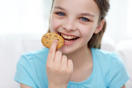 galletas: personas, infancia feliz, comida, dulces y concepto de panadería - niña come la galleta o una galleta sonriente Foto de archivo