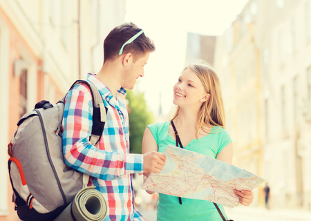 mochila de viaje: travel, vacation and friendship concept - smiling couple with map and backpack in city
