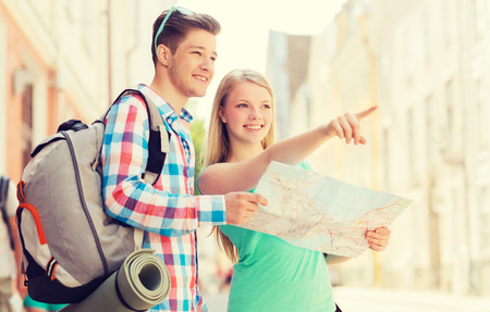 niño con mochila: travel, vacation and friendship concept - smiling couple with map and backpack in city