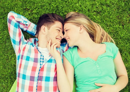 love park: holidays, vacation, love and friendship concept - smiling couple lying on blanket in park Stock Photo