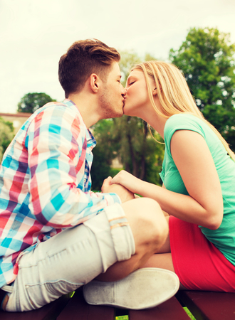 love kissing: holidays, vacation, love and friendship concept - smiling couple kissing in park