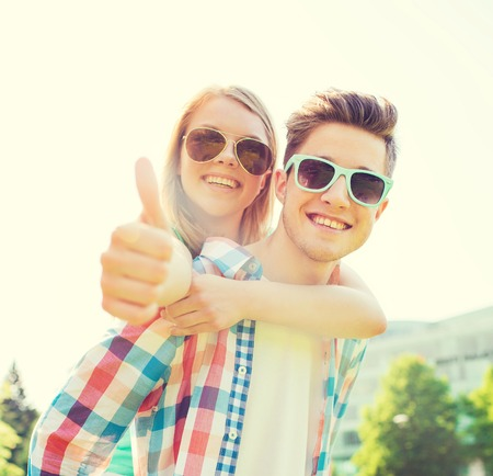teenage love: summer holidays, vacation, love, gesture and friendship concept - smiling teen couple in sunglasses having fun and showing thumbs up in park Stock Photo