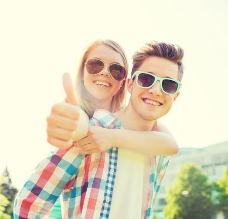 zomervakantie, vakantie, liefde, gebaar en vriendschap concept - lachende tiener paar in zonnebril plezier en zien thumbs up in het park