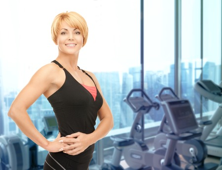 people, fitness and sport concept - happy woman fitness instructor over gym machines background photo