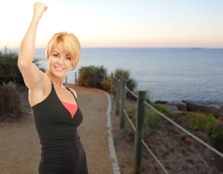 people, fitness, gesture, success and sport concept - happy woman with raised hand outdoors over beach sunset background photo