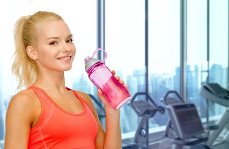 fitness gym: people, sport, fitness and recreation concept - happy woman drinking water from bottle over gym machines background Stock Photo