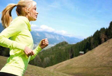 Fitness, Sport, Menschen, Technologie und gesunden Lifestyle-Konzept - glückliche junge Frau mit Kopfhörern Joggen oder Laufen über Berge und blauen Himmel im Hintergrund