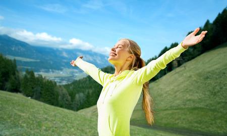 fitness, deporte, las personas y las emociones concepto - mujer feliz en ropa deportiva disfrutando del sol y la libertad sobre las montañas, campos verdes y el cielo azul de fondo Foto de archivo
