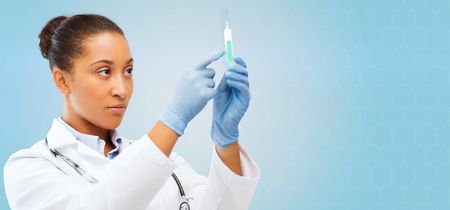 healthcare, vaccination, anesthesia and medical concept - african american female doctor holding syringe with injection over blue background
