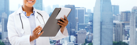 happy african: health care, people and medical concept - happy african female doctor with clipboard over city background Stock Photo
