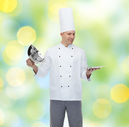 cloche: cooking, profession and people concept - happy male chef cook opening cloche cover over green lights background