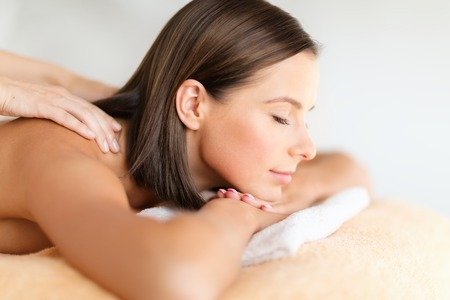 relaxation massage: health, beauty, resort and relaxation concept - beautiful woman with closed eyes in spa salon getting massage