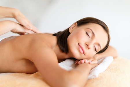 beauty eyes: health, beauty, resort and relaxation concept - beautiful woman with closed eyes in spa salon getting massage