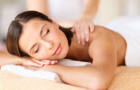beauty resort: health, beauty, resort and relaxation concept - beautiful woman with closed eyes in spa salon getting massage