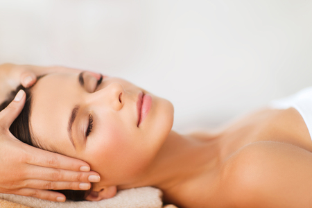 spa, resort, beauty and health concept - beautiful woman in spa salon getting face treatment