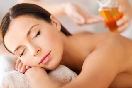 beauty and spa concept - beautiful woman in spa salon getting oil treatment Stock Photo