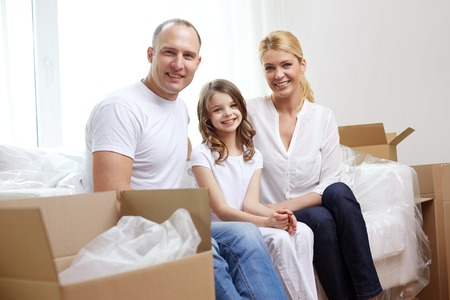 moving: family, children, accommodation and people concept - happy family with boxes moving to new home