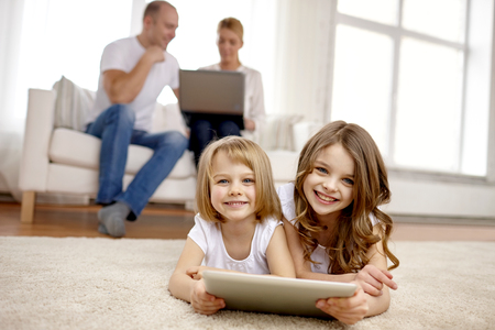 pre teen: people, family, technology and children concept - happy little girls playing with tablet pc computer at home Stock Photo